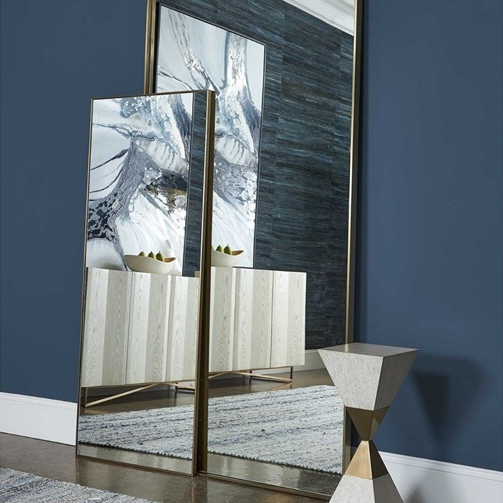 Deep blue walls with gold mirrors and marble side stand decor